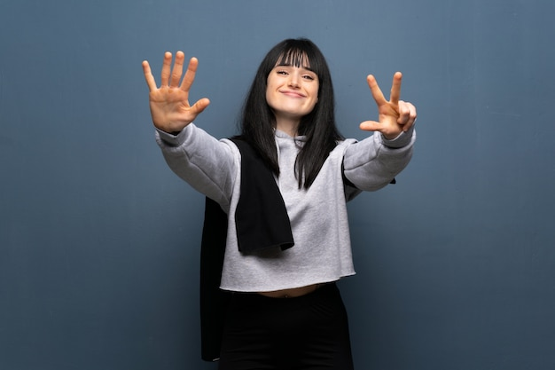 Young sport woman counting eight with fingers