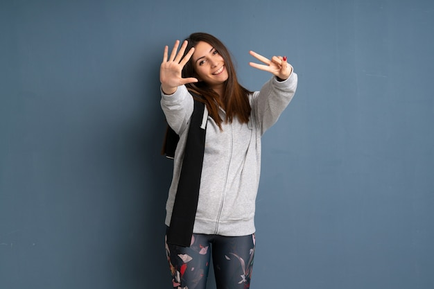 Young sport woman counting seven with fingers