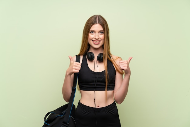 Young sport woman giving a thumbs up gesture