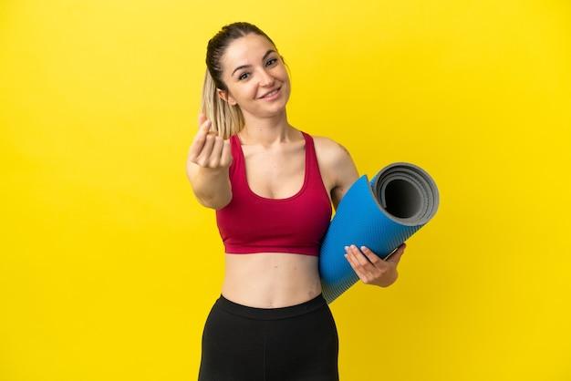 Молодая спортивная женщина идет на занятия йогой, делая денежный жест