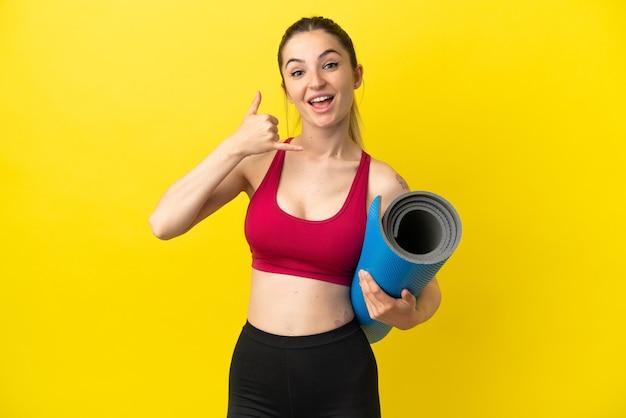 Молодая спортивная женщина собирается на занятия йогой, удерживая циновку, делая телефонный жест. перезвони мне знак