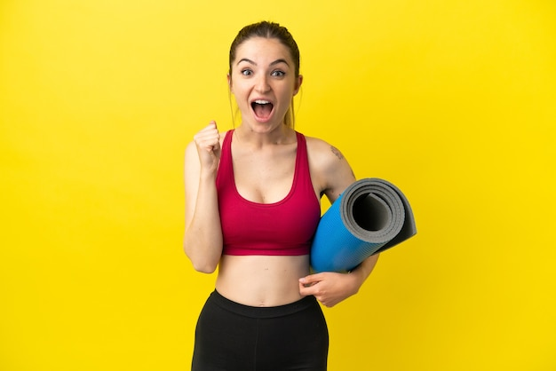 Young sport woman going to yoga classes while holding a mat celebrating a victory in winner position