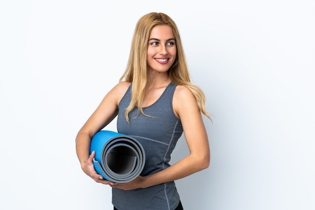 Young sport woman going to yoga classes while holding a mat over isolated white wall