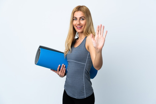 Young sport woman going to yoga classes while holding a mat over white wall saluting with hand with happy expression