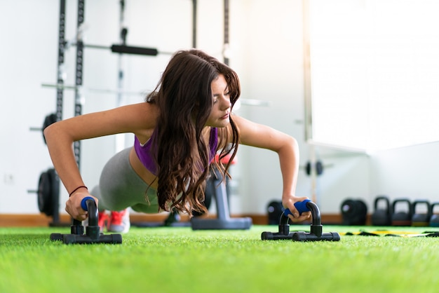 Young sport woman in a gym doing push-ups