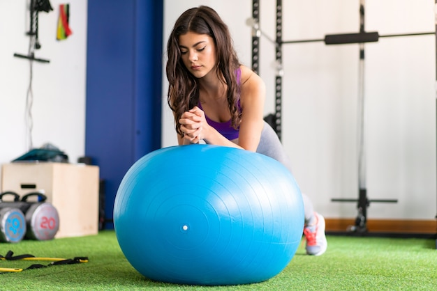 Young sport woman in a gym with fit ball