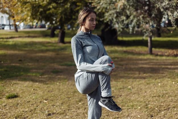 スポーツスーツを着た若いスポーツ女性が秋の公園でウォーミングアップ