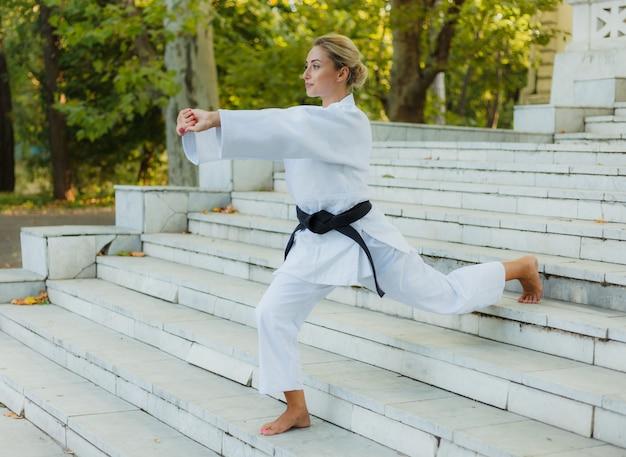 Молодая спортивная женщина в белом кимоно с черным поясом делает разминку на лестнице перед тренировкой. боевые искусства, самооборона