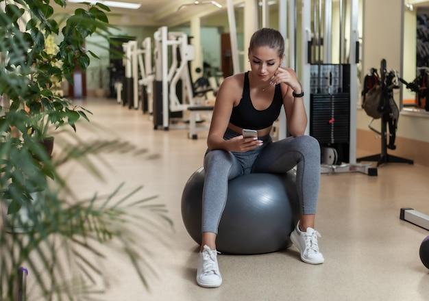 체육관에서 맞는 공에 앉아있는 동안 스마트 폰을 사용하는 운동복에 젊은 스포츠 여자. 운동 휴식. 건강한 라이프 스타일 컨셉
