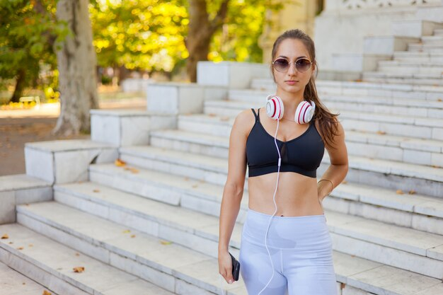 헤드폰 야외 포즈와 운동복에 젊은 스포츠 여자
