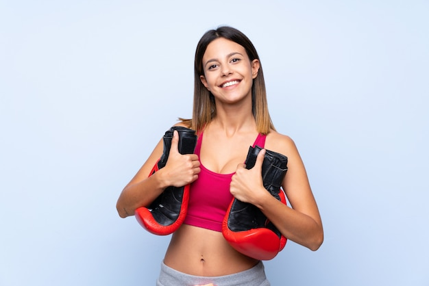 Young sport woman over isolated blue wall with boxing gloves