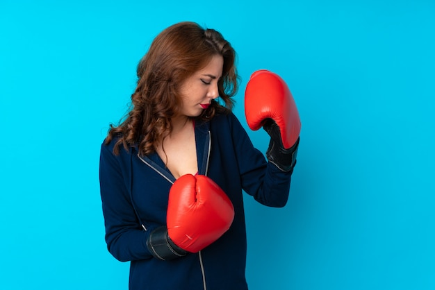 Young sport woman over isolated blue wall