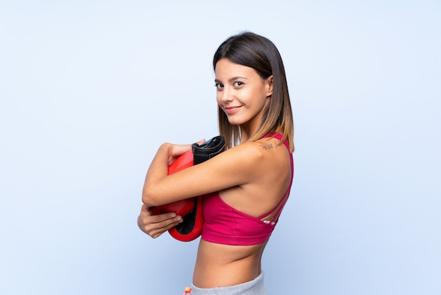 Young sport woman over isolated blue  with boxing gloves