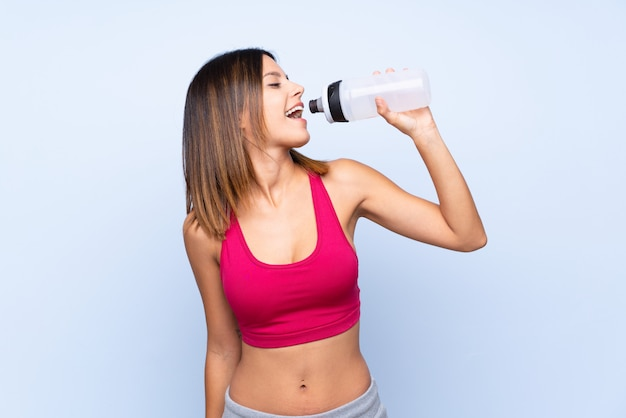 Young sport woman over isolated blue with sports water bottle