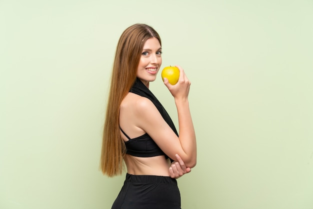 Young sport woman over isolated green background with an apple