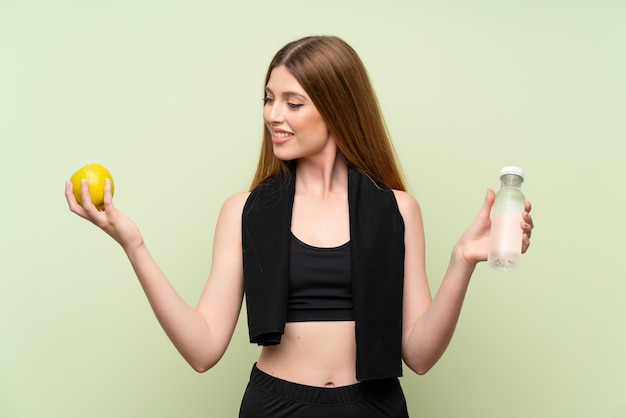 Young sport woman over isolated green with an apple