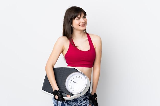 体重計と白い壁に分離された若いスポーツ女性