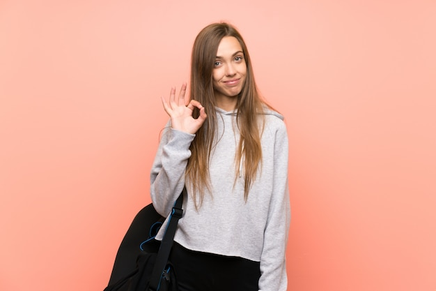 Young sport woman over isolated pink  showing an ok sign with fingers