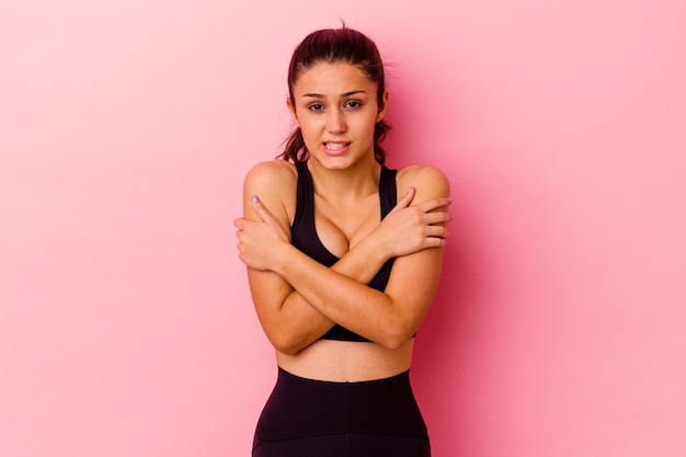 Young sport woman isolated on pink wall going cold due to low temperature or a sickness