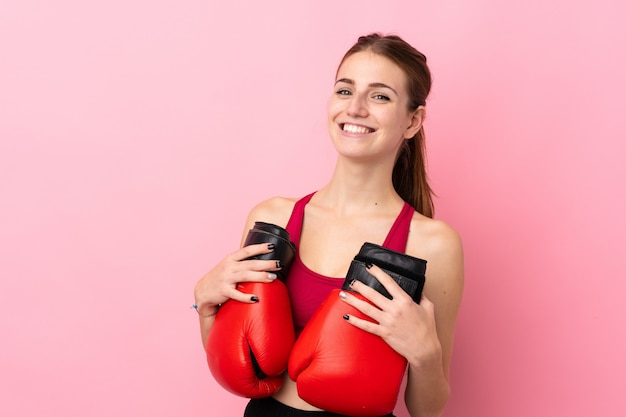 Young sport woman over isolated pink wall with boxing gloves