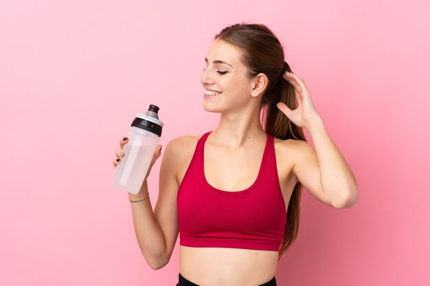Young sport woman over isolated pink wall with sports water bottle