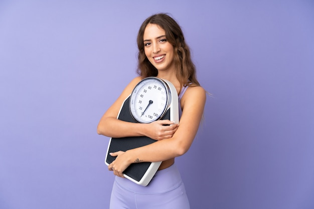 Young sport woman over isolated purple wall with weighing machine