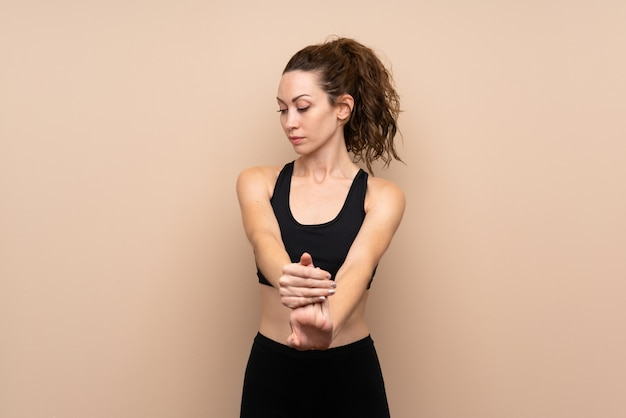Young sport woman over isolated stretching arm