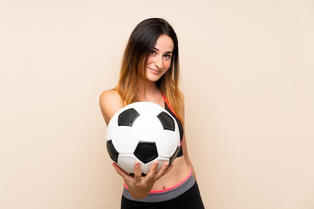 Young sport woman over isolated wall holding a soccer ball