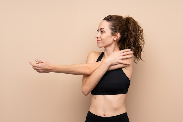 Young sport woman over isolated wall stretching arm