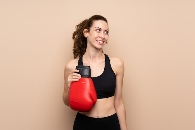 Young sport woman over isolated wall with boxing gloves