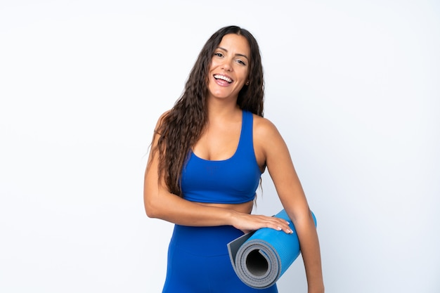 Young sport woman over isolated white background with a mat and smiling