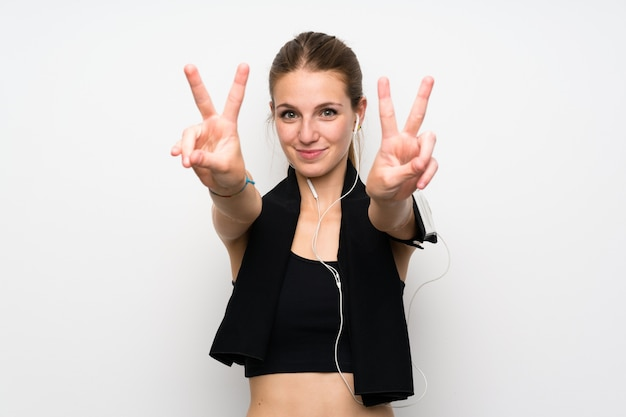 Young sport woman over isolated white wall smiling and showing victory sign