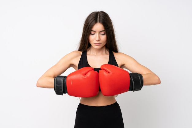 Young sport woman over isolated white wall with boxing gloves