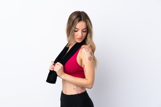 Young sport woman over isolated white wall with sport towel