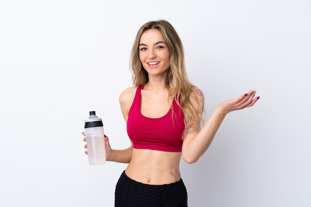 Young sport woman over isolated white wall with sports water bottle