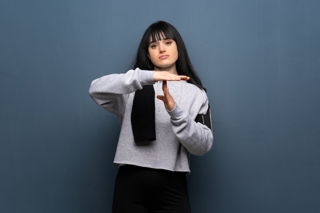 Young sport woman making time out gesture