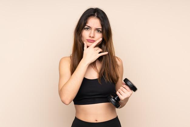 アイデアを考えてベージュの壁に分離された重量挙げを作る若いスポーツ女性