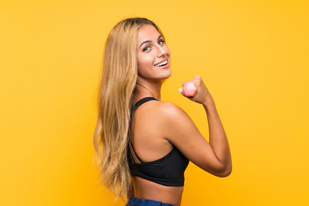 Young sport woman making weightlifting over isolated wall
