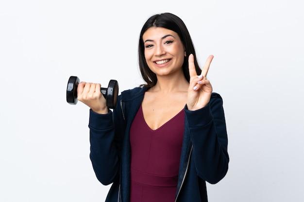 Молодая спортивная женщина, делающая поднятие тяжестей над изолированной белой улыбкой и показывающая знак победы