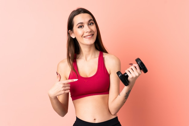 Young sport woman making weightlifting over pink wall with surprise facial expression