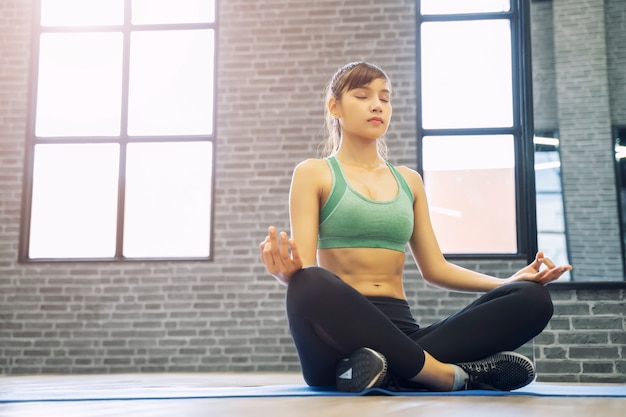 Young sport woman making yoga pose at gym