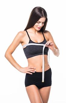 Молодая спортивная женщина измеряет идеальное спортивное тело на белом фоне