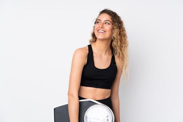 計量機で白い壁に若いスポーツ女性