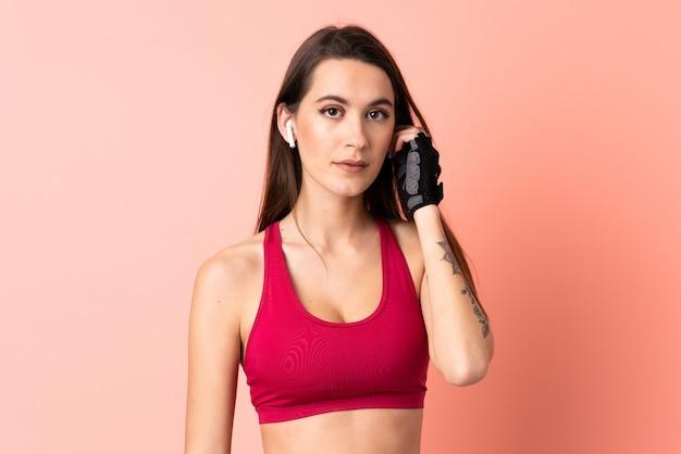 音楽を聴いて孤立したピンクの壁の上の若いスポーツ女性