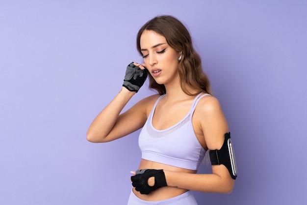 音楽を聴く紫色の壁を越えて若いスポーツ女性