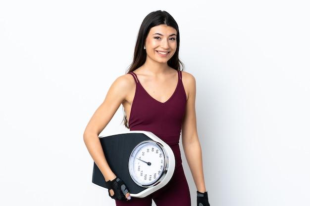 計量機と白い壁の上の若いスポーツ女性