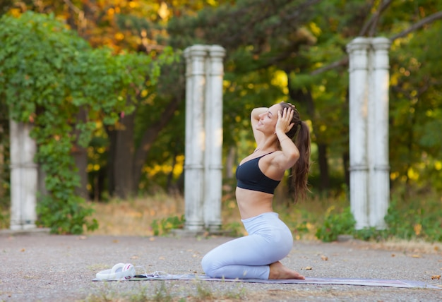 Young sport woman posing on camera while sitting on a yoga mat. outdoor workout