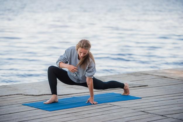 ビーチでヨガの練習の若いスポーツ女性
