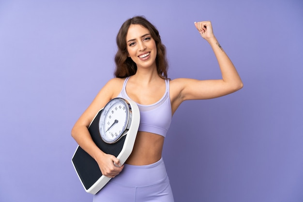 Young sport woman over purple wall holding a weighing machine and doing strong gesture