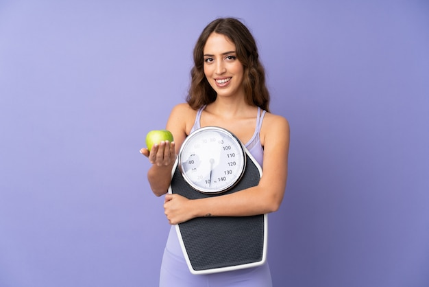 Young sport woman over purple wall holding weighing machine and offering an apple